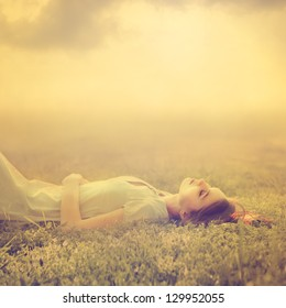 beautiful young girl dreams of lying on a magic meadow in spring
