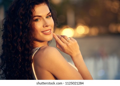 Beautiful young girl in dress and curly hair smiling at sunset