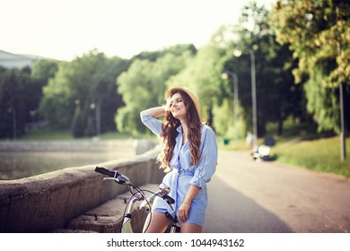 A beautiful young girl in dress riding a bicycle through the city outdoors. copyspace