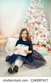 beautiful young girl in a dress sitting near the New Year tree with a gift in hand