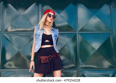 Beautiful young girl dressed in stylish street style outfit posing in front of a green tin background. Dressed in black with a denim vest, red baseball cap, sunglasses and with choker around her neck.