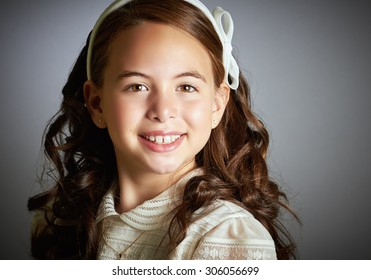 Beautiful young girl dressed in white. First Communion. Perfect teeth and smile, long curly hair. Dark background, close up studio shoot.