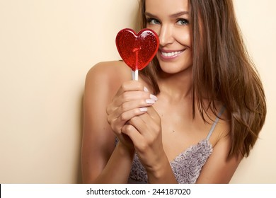 Beautiful young girl in a dressing gown of silk and lace with thin spaghetti straps with a cut and bow in front of hands holding lollipop in the shape of a red heart looking into camera valentines day