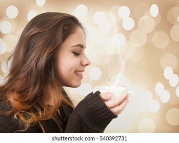 Beautiful Young Girl Drinking Tea or Coffee. Young Lady holding cup of coffee over brown background with highlights