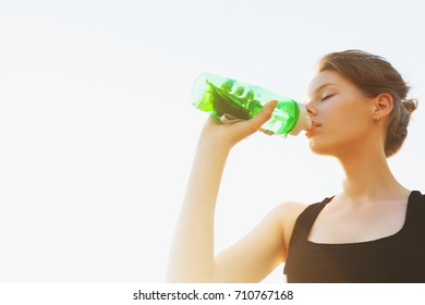 Beautiful young girl is drinking water on sports training. Positive summer photo