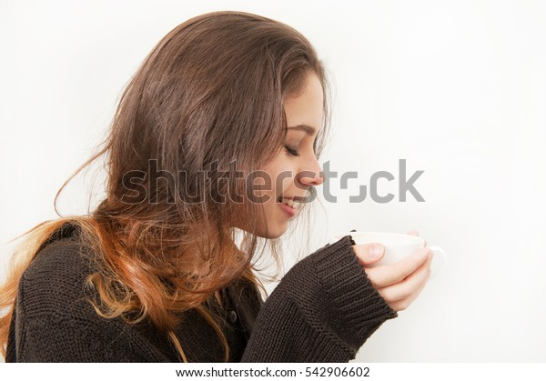 Beautiful young girl drinks coffee on a white background