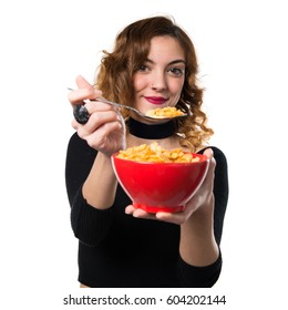 Beautiful young girl eating cereals from a bowl