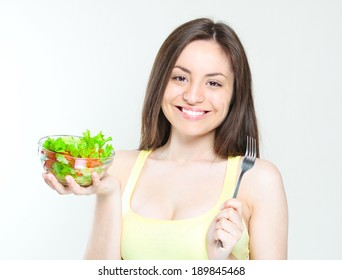 beautiful young girl eating salad. smiling happy girl eating healthy food.