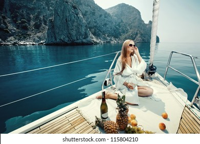 beautiful young girl eating and talking on a mobile phone on a boat sailing along the rocky shore of the sea