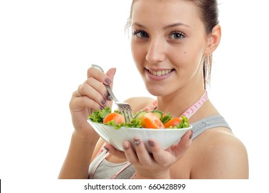 beautiful young girl eats a salad and smiles on camera