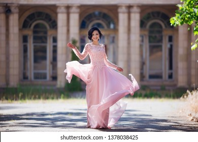 Beautiful young girl with elegant dress and nice smile walking in the street. Lifestyle concept. Youth and happiness.