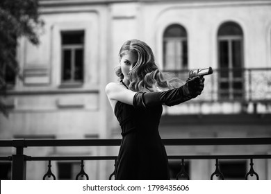Beautiful young girl in an elegant dress. Woman holding a gun in her hands. Fashion model in the form of a dangerous sexy spy. Black and white photography. Retro lady, vintage hairstyle evening makeup