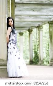 Beautiful young girl in elegant dress in summerhouse