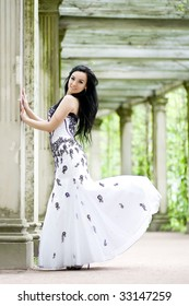 Beautiful young girl in elegant dress in ancient summerhouse