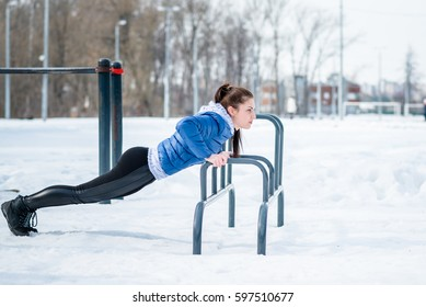 A beautiful young girl is engaged in stretching and gymnastics in the winter forest, on the sports field.