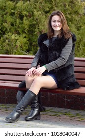 Beautiful young girl enjoying life in the park on beautiful sunny day, wearing furry coat and pom pom hat. Successful young woman. The concept of happiness and a good life