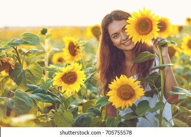 Beautiful young girl enjoying nature on the field of sunflowers at sunset