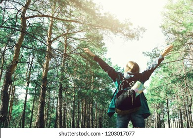 Beautiful young girl with equipment is standing in the forest. Backpack with map inside. Travel concept. Tourist widely spread his arms in connection with nature