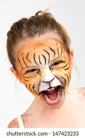 Beautiful young girl with face painted like a tiger