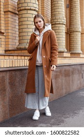 Beautiful young girl in fashionable beige hoodie, elegant brown camel coat and pants on brick wall background. Walking on the street.