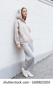 Beautiful young girl in fashionable beige hoodie and pants on light background. Walking on the street.