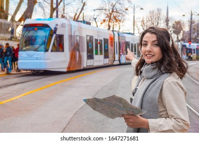 Beautiful young girl in fashionable clothes with map Tramway vehicle in Istanbul,Turkey.Traveler woman  lifestyle Concept.