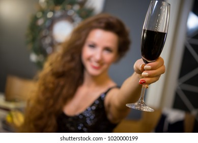 Beautiful young girl in festive attire with a glass of red wine. girl is blurry