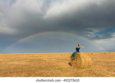 Beautiful young girl in a field with straw on a background of rainbow