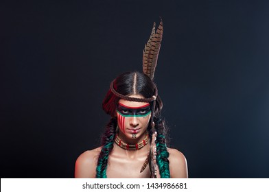 Beautiful young girl in fighting colors Indians Apaches. Fashion and beauty portraits of a beautiful Indian girl.