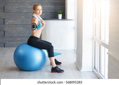 Beautiful young girl with fit ball at home. Fitness woman working out with pilates ball, relax and resting after workout with towel on neck