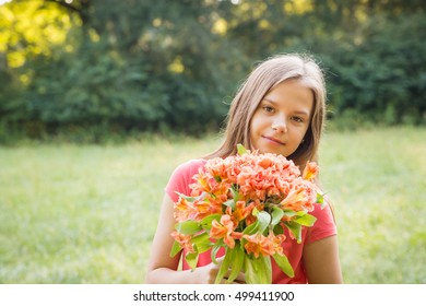 Beautiful young girl with flower bouquet in a nature setting with blurred background