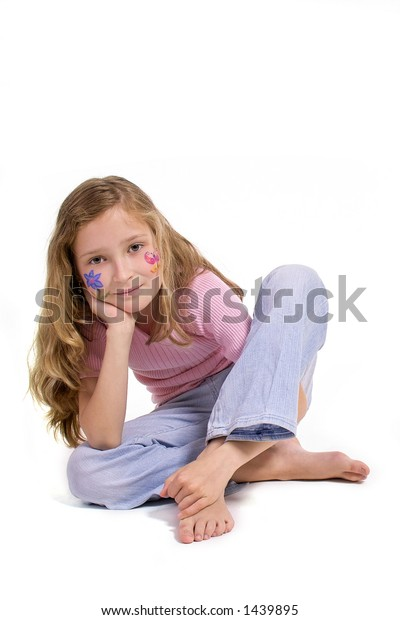 beautiful young girl with a flower and butterfly drawing on her cheek sitting on the floor looking direct