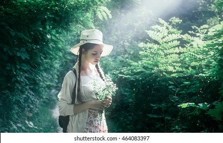 beautiful young girl with flowers in their hands, walking along the forest paths in the early morning