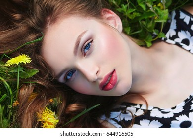 A beautiful young girl with flowing wavy chestnut hair lies on the grass against a background of blooming yellow flowers. Natural makeup, pink lips, light skin. Beauty. Health, fashion. Nature.