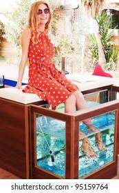 Beautiful young girl gets fish spa procedure in a beautiful blue water