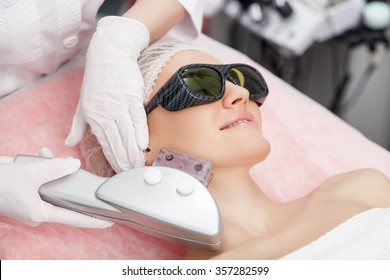 Beautiful young girl is getting laser treatment on her face. She is lying and smiling. The woman is wearing goggles