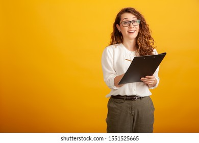 Beautiful young girl in glasses with a clipboard smiles and looks in camera standing isolated on yellow background