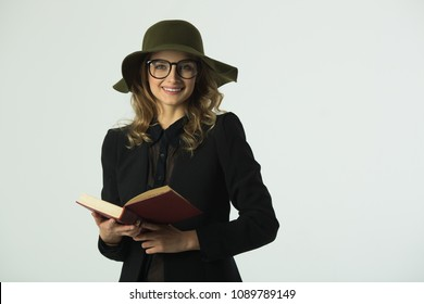 beautiful young girl with glasses and hat reading a book on a white background