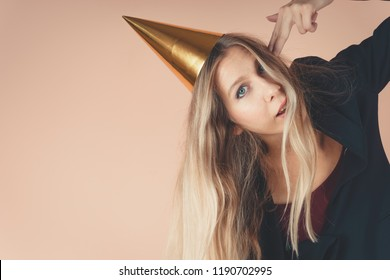 Beautiful young girl in a golden cap stands opposite the pink wall. Concept office businesswoman with atypical accessory. Model shows hands with a gun and shows fatigue
