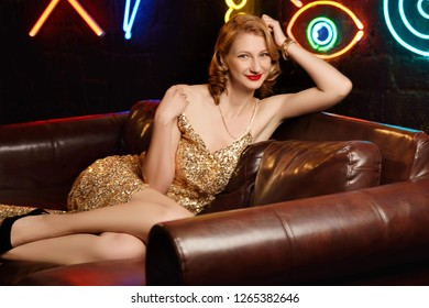Beautiful young girl in golden evening dress