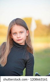 Beautiful Young Girl at the Golf Course.  A portrait of a junior golfer standing in front of a white golf flag.