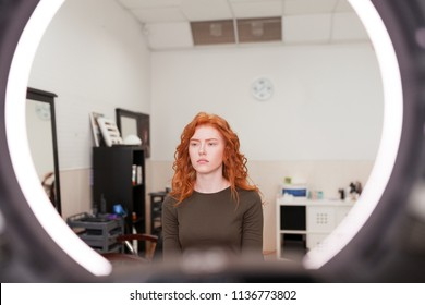 Beautiful young girl got correction of eyebrows in a beauty salon. Woman correcting eyebrows form. Portrait of a beautiful red-haired girl