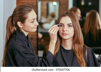 Beautiful young girl got correction of eyebrows in a beauty salon