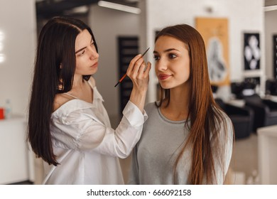 Beautiful young girl got correction of eyebrows in a beauty salon. Woman correcting eyebrows form