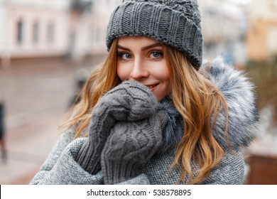 Beautiful young girl in a gray knitted hat and mittens, outdoors