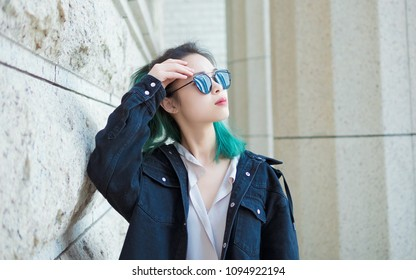 08ed6e40379 Beautiful young girl with green hair posing outdoor. Sunny portrait of  glamour Chinese stylish lady