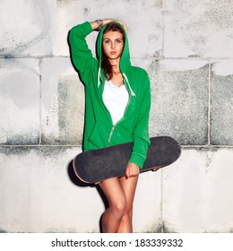 beautiful young girl in green hoodie with and skateboard against  grey wall