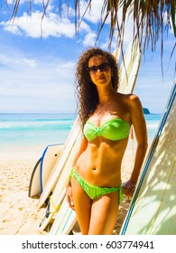 A beautiful young girl in a green swimsuit in sunglasses stands near the surfboards on the background of the beach and the blue ocean. A hot day in a warm, sunny tropical country - Thailand