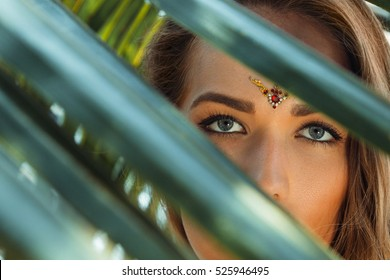 Beautiful young girl with grey eyes and bindi behind palm leaves.