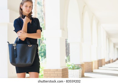 Beautiful young girl with a handbag outdoors (with copy space)